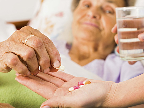 A caregiver gives a female patient medicine with a glass of water