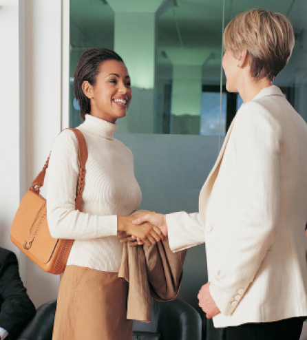 Two females shake hands after an interview