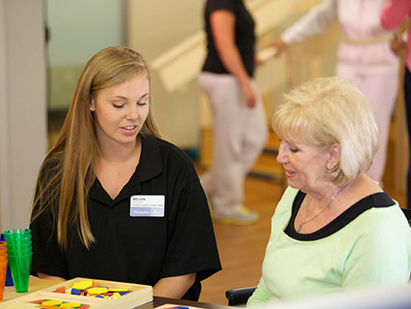 A female caregiver helps a patient with speech therapy