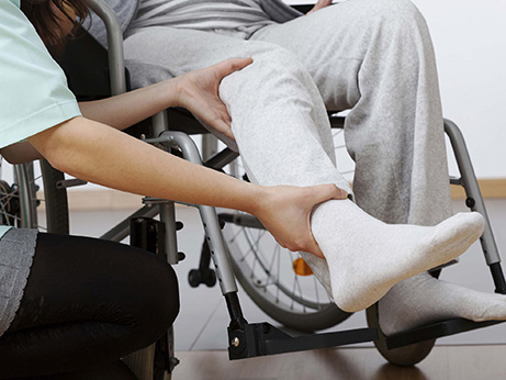 A caregiver helps a senior rehab patient put foot on foot pedals