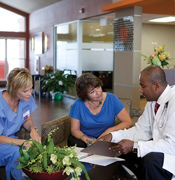 a doctor and nurse meet with a family member to go over treatment