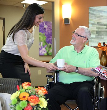 a caregiver gives a senior rehabilitation patient a cup of coffee