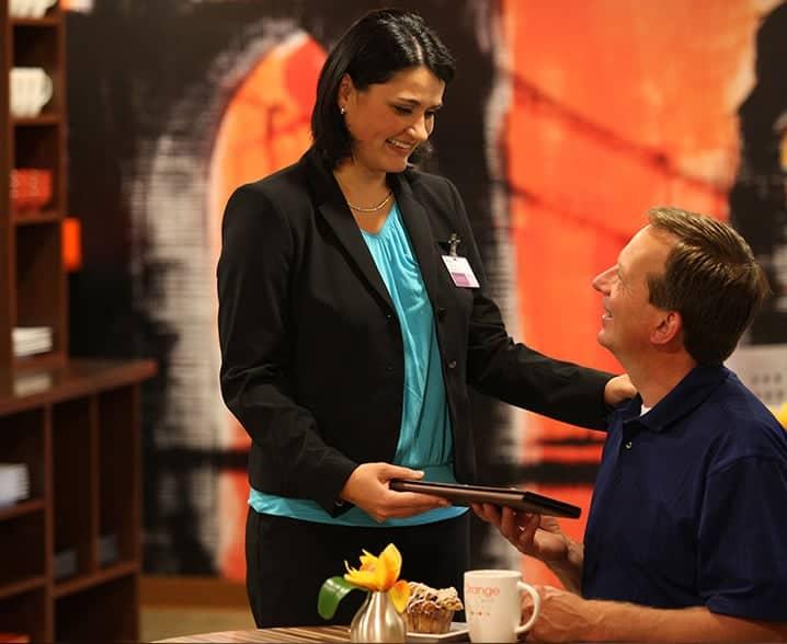 a concierge brings a guest his check at Orange Spot Bistro