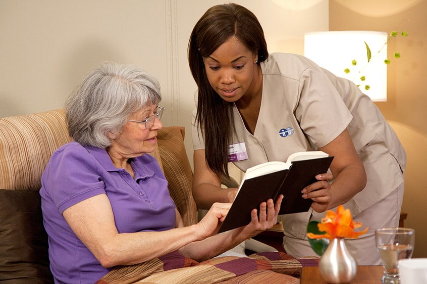 a caregiver helps a patient read a book